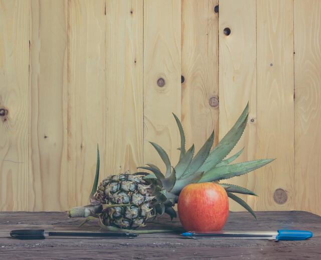 Pen-Pineapple-Apple-Pen on wooden background.